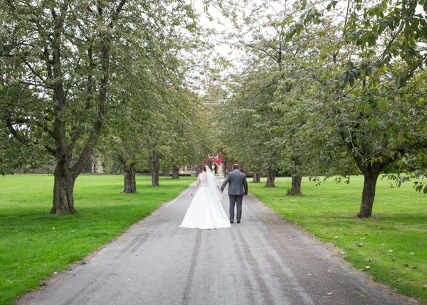 Bride and Groom walking through a line of trees at Thoresby Courtyard Wedding