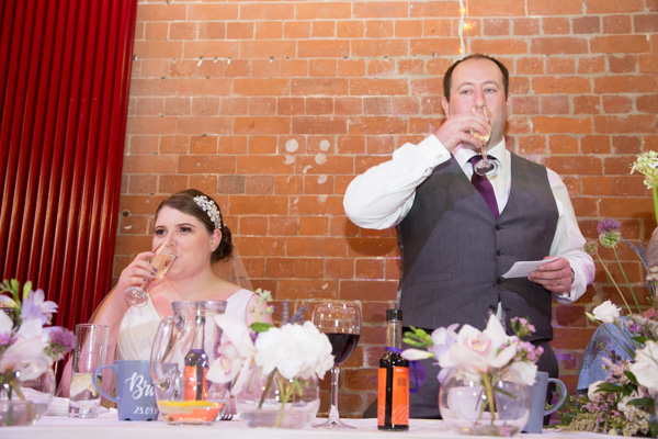 Bride and groom drinking a toast during the wedding speeches