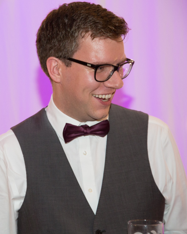 Bridesman laughing in front of light up purple backdrop