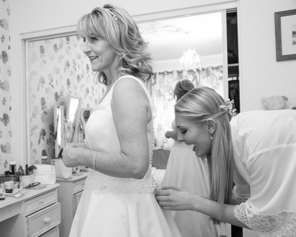 Bridesmaid fastening Bride's dress while laughing