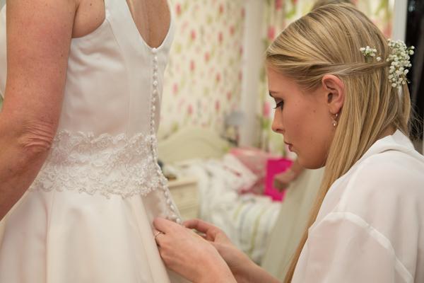 Bridesmaid fastening Bride's dress