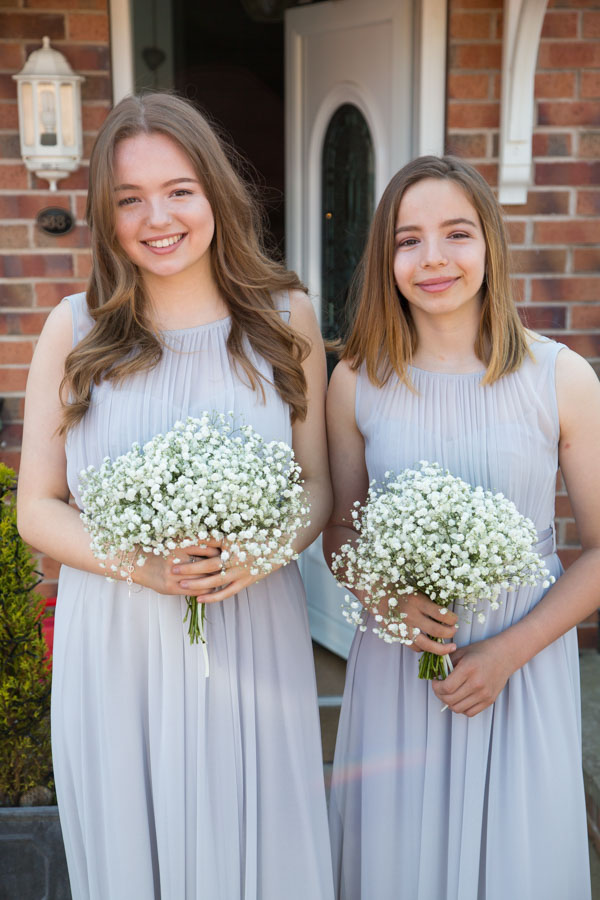 Two bridesmaids in grey dresses holding bouquets