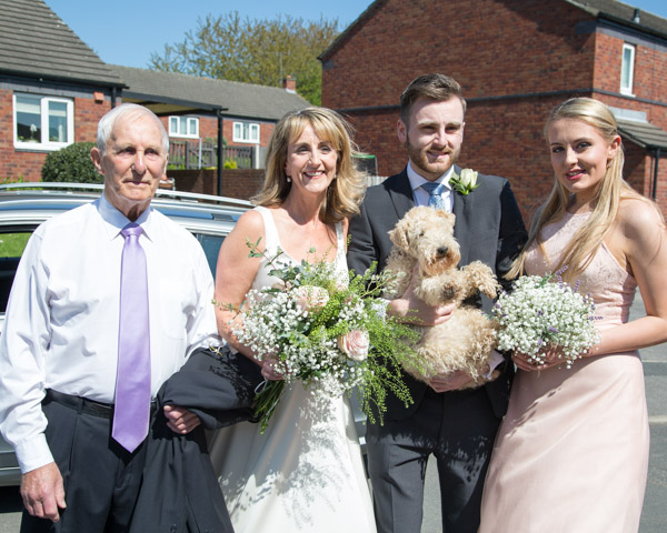 Bride, Father, Bridesmaid and son outside house ready to get in car.