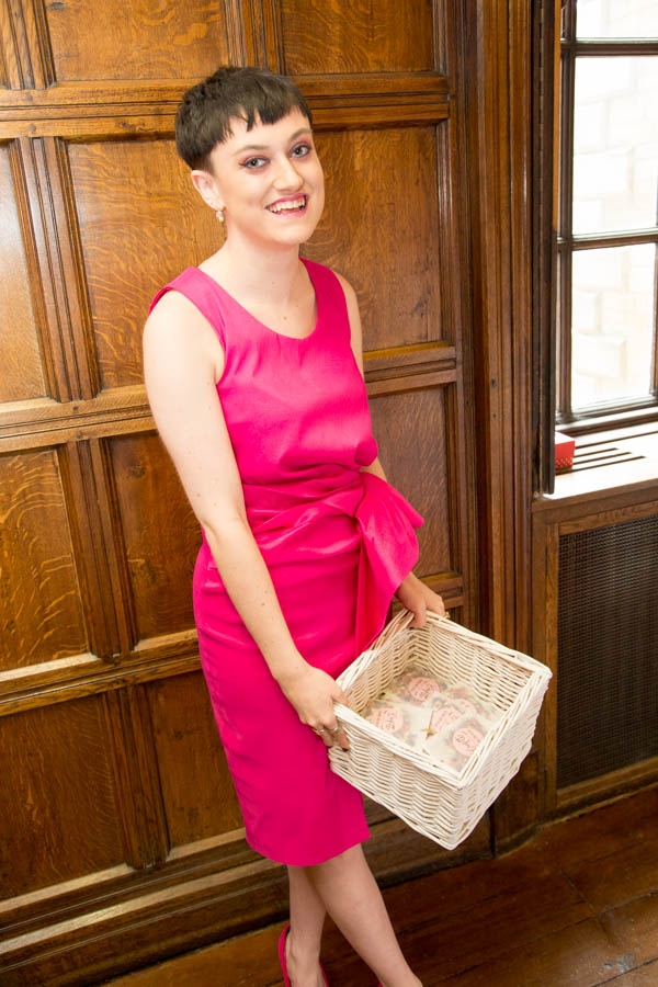 Guest at the Cannon Hall wedding in a pink dress smiling with a basket of confetti.