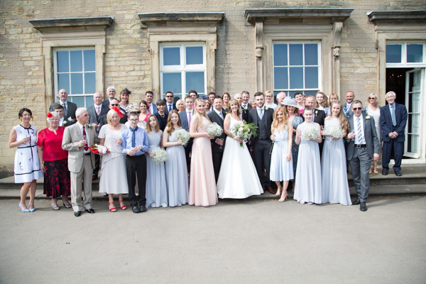 All the wedding guests outside of Cannon hall smiling for a group photo.
