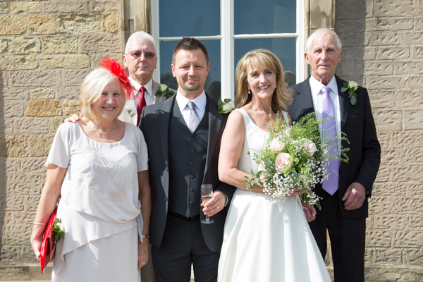 Bride, Groom and Parents smiling outside of Cannon Hall on the wedding day