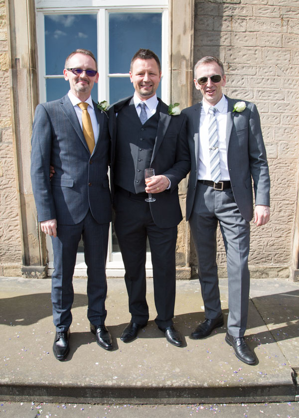 Groom and his brothers smiling outside of Cannon hall wedding