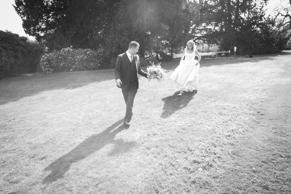 Bride and groom walking across the grass at Cannon Hall with groom holding bride's flowers in black and white