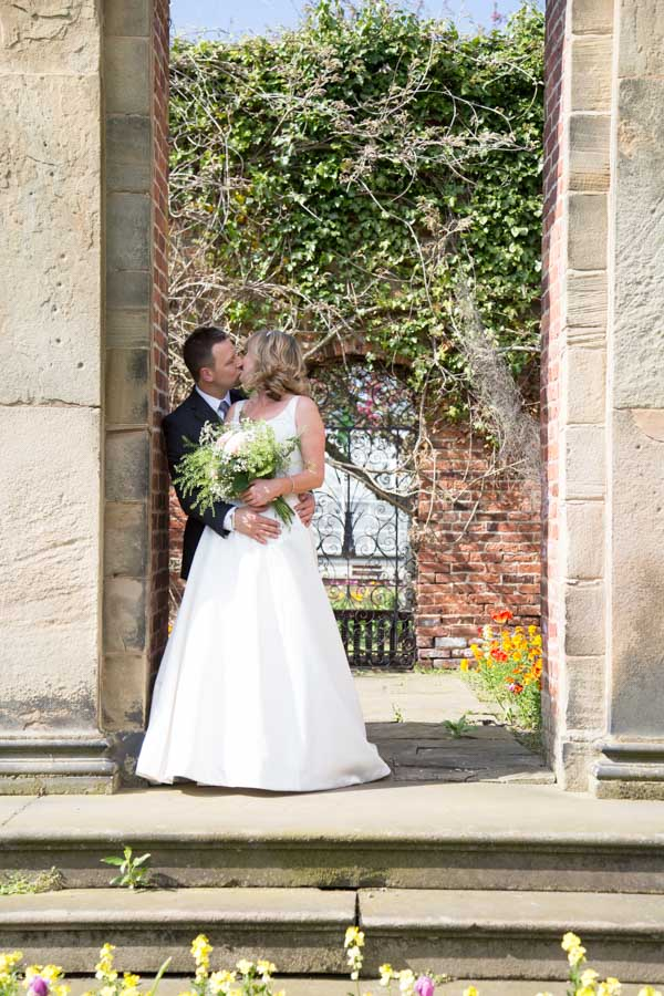 Bride and Groom kiss in the walled garden at Cannon Hall