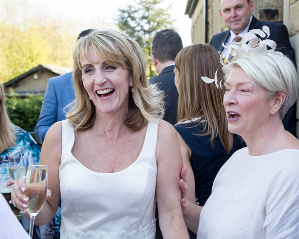 Bride and guest laughing outside Cawthorne Village Hall