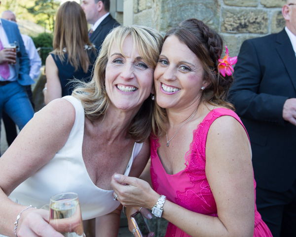 Bride and guest wearing a pink dress outside Cawthorne Village Hall