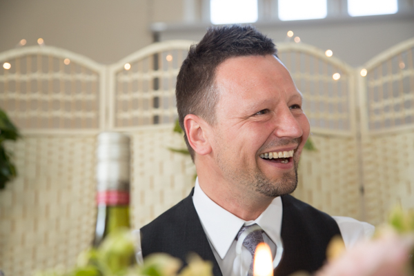 Groom laughing during the speeches at Cawthorne Village Hall