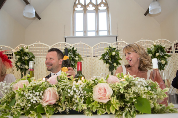 Bride and groom laughing during a speech at Cawthorne Village Hall