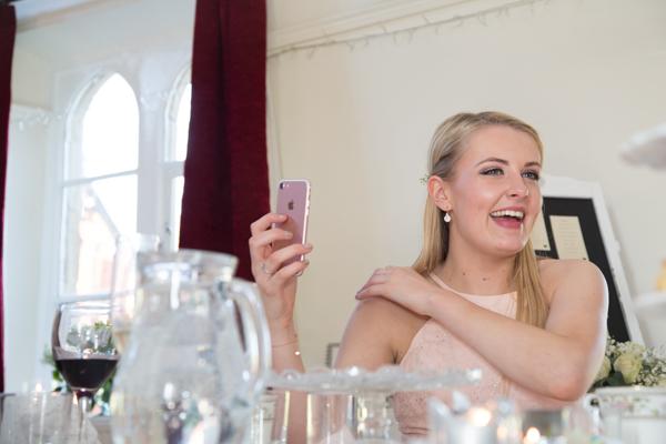 Bridesmaid laughing and recording the speeches at Cawthorne Village Hall