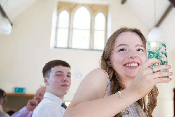 Bridesmaid taking pictures during the speeches at Cawthorne Village Hall