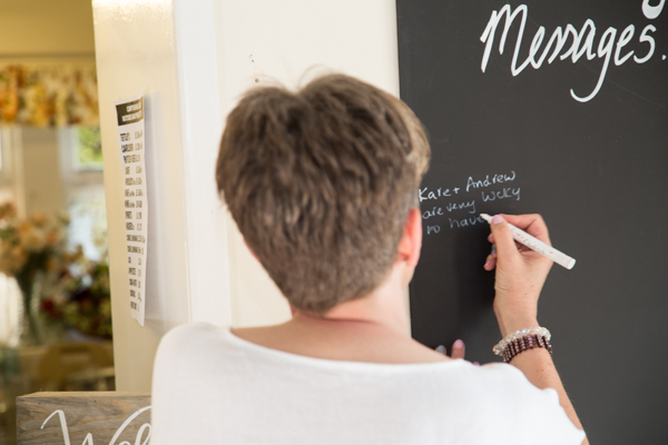 Wedding guest writing on the blackboard at Cawthorne Village Hall