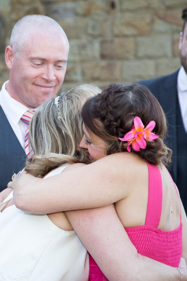 Bride hugging wedding guest outside Cawthorne village hall