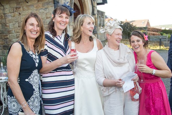 Bride with her work friends standing outside Cawthorne Village Hall