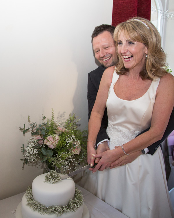 Bride and Groom cutting the cake and laughing at Cawthorne Village Hall