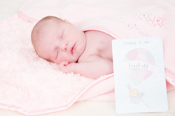Baby laid on pink blanket next to 1 week old milestone card.