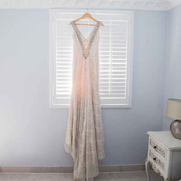 Bridal gown hanging in front of a window Barnsley wedding photography