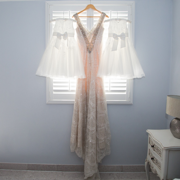 Bridesmaid and wedding dress hanging by a window Barnsley wedding photography