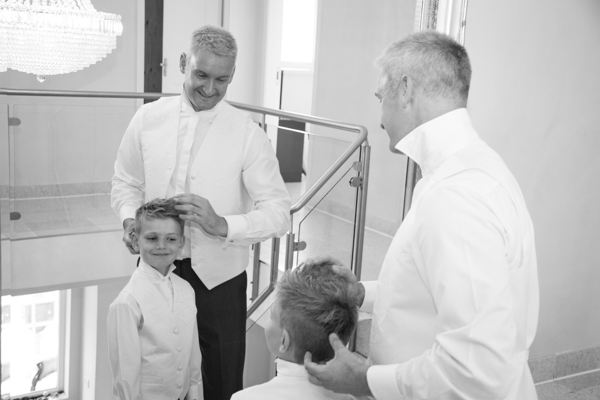 Groom fixing best man's hair at Millhouse Green accommodation