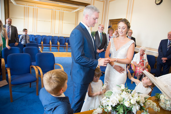 Bride and Groom exchanging rings with their children by their side