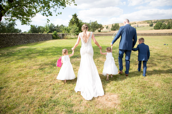 Bride and Groom walking through the garden with their children