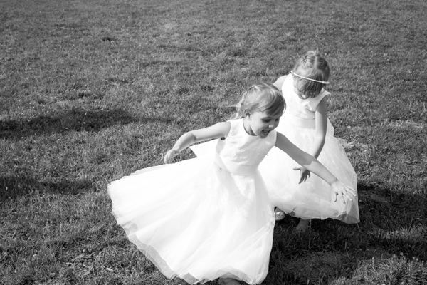 Bridesmaids running through the garden and playing in white dresses Barnsley wedding photography