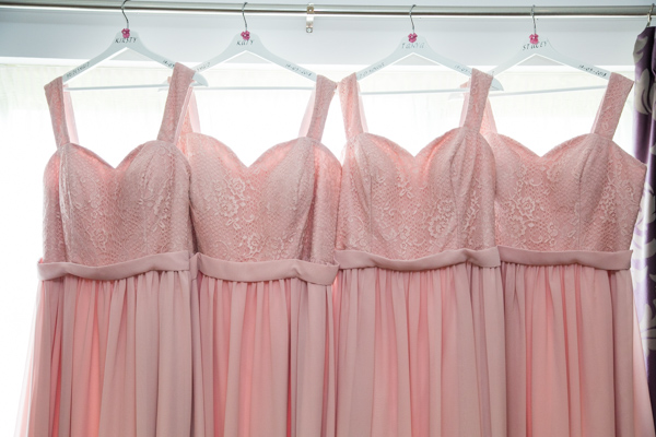 Pink bridesmaid dresses hung on personalised hangers at Burntwood court hotel.