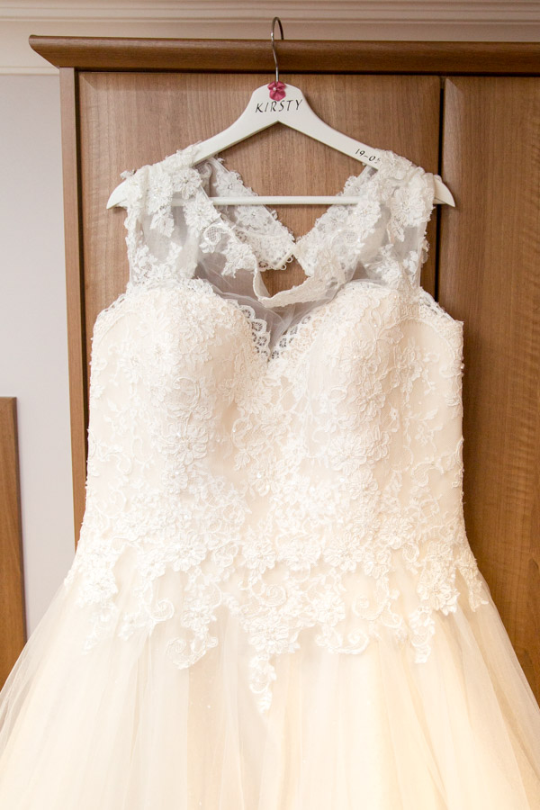 Wedding dress hanging on a personalised hanger against a wooden wardrobe at Burntwood court hotel