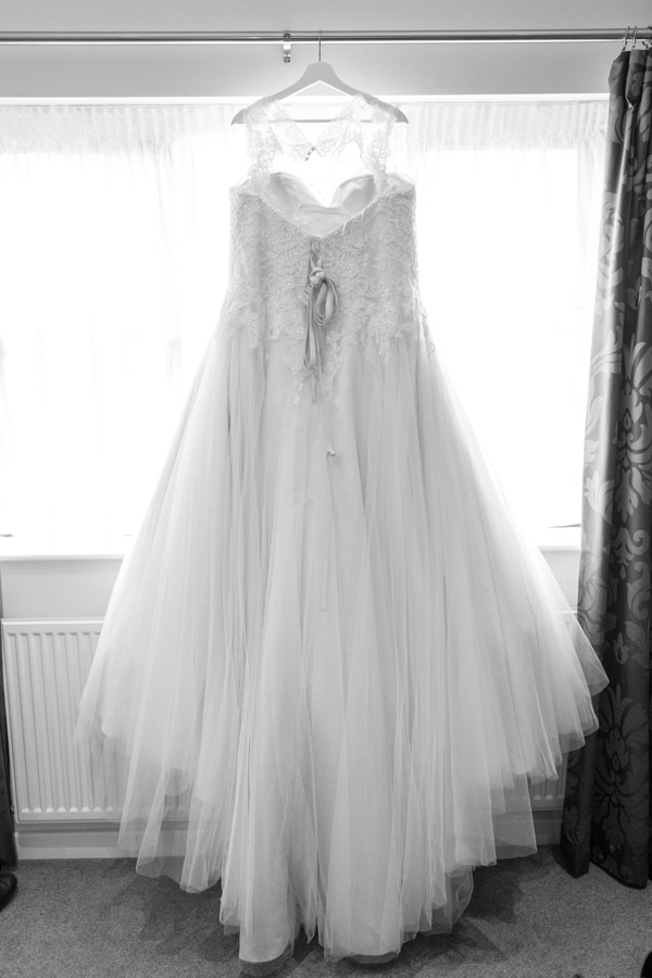 Wedding dress hanging on a personalised hanger against a window at Burntwood court hotel.