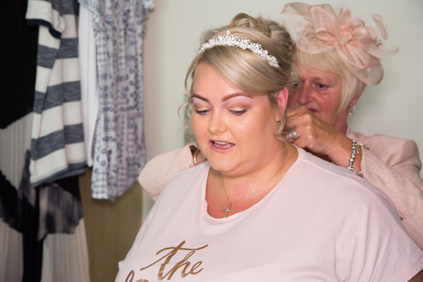 Mother of the bride fastening brides necklace on the morning of the wedding
