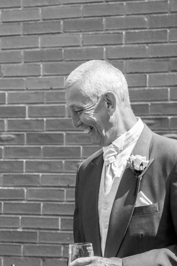 Father of the groom laughing with a pint on the morning of the wedding