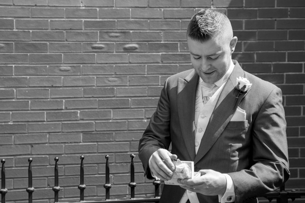 Groomsman holding the wedding rings outside The Burntwood