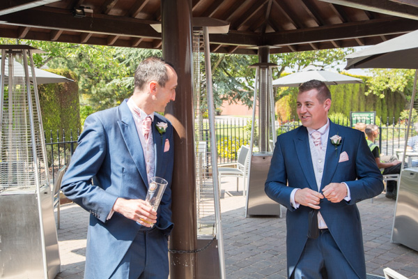 Groom and Best man talking on the patio outside The Burntwood