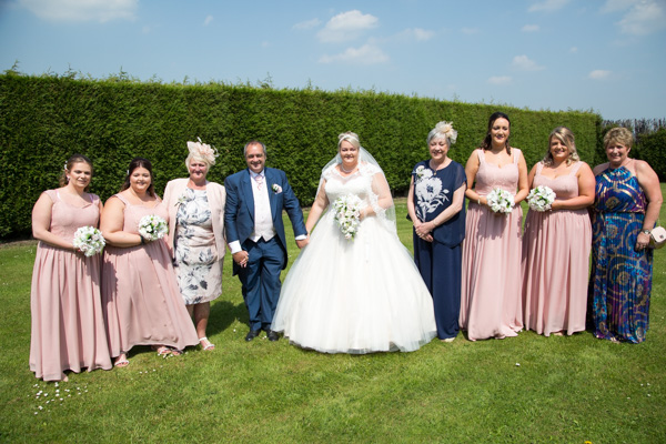 Bridal party on the grassed area at the back of the hotel rooms at Burntwood Court Hotel