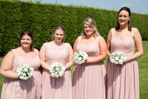 Bridesmaids in pink with rose bouquets at the back of the hotel rooms at Burntwood court