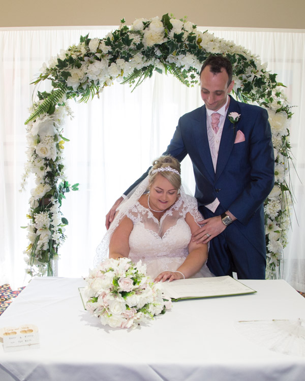 Bride and Groom sign the register at the Qube in Burntwood court Hotel