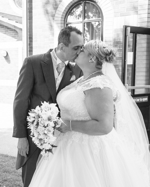 Bride and Groom kiss outside the Qube at Burntwood Court Hotel