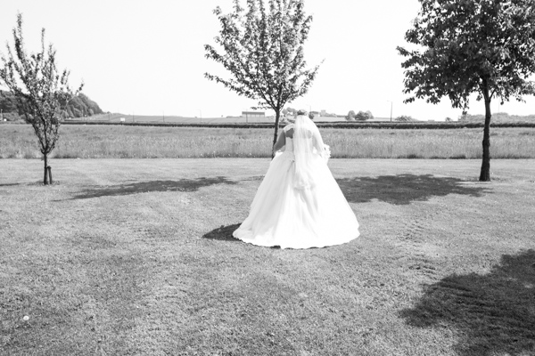 Bride walking through the grounds of Burntwood Court Hotel
