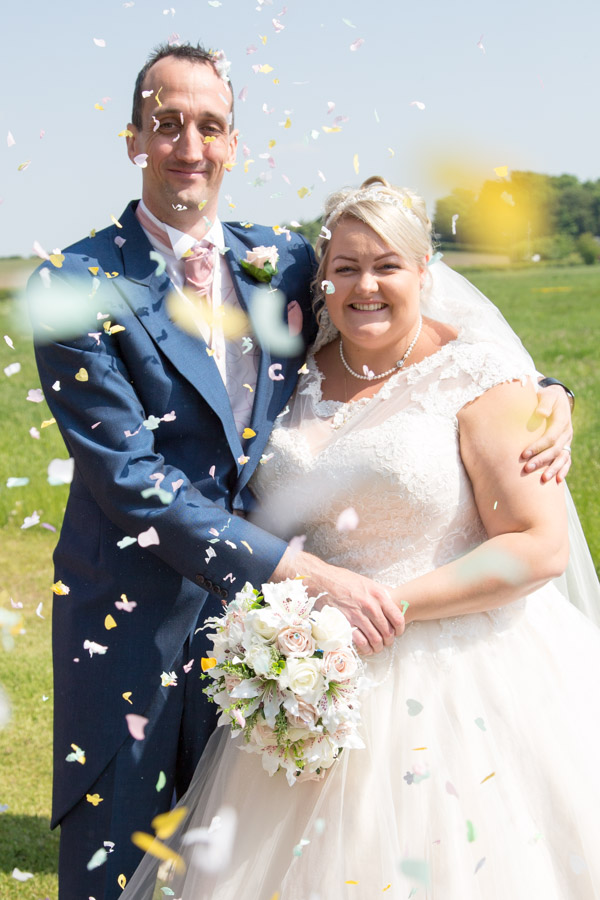 Bride and Groom with confetti at Burntwood Court hotel