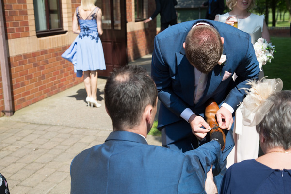 Best man tying grooms shoe lace