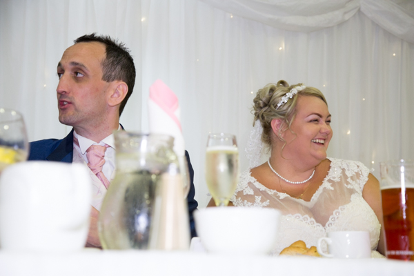 Bride and Groom laughing at speeches at the top table in the Qube Burntwood Court Hotel