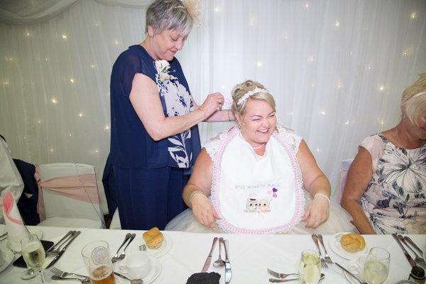 Mother of the Groom tying bib around Brides neck at Burntwood Court Hotel weding