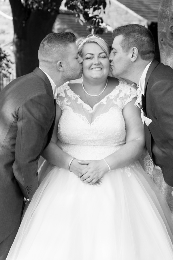 Bride being kissed on both cheeks by the best men