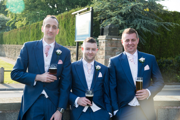 Groomsmen standing against the wall at Burntwood Court Hotel with a pint each