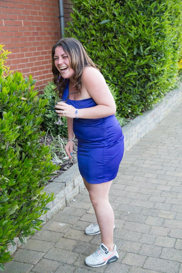 Wedding guest laughing in a dress wearing trainers