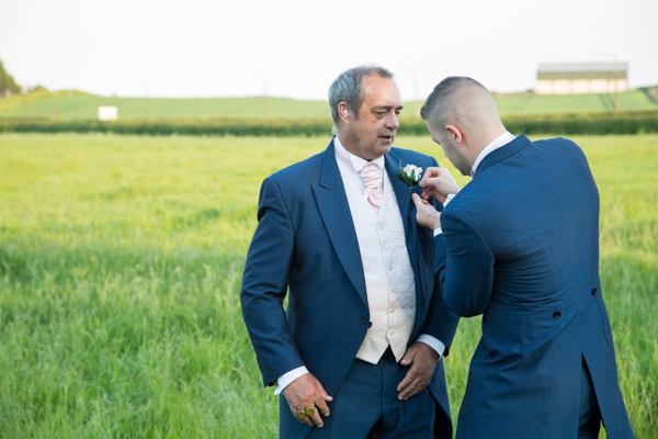 Best man fixing father of the brides buttonhole